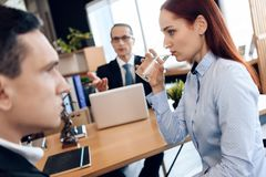 Young red-haired woman is drinking glass of water, sitting next to adult man in divorce lawyer`s office. Young red-haired women is drinking glass of water Royalty Free Stock Photo