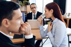 Young red-haired woman is drinking glass of water, sitting next to adult man in divorce lawyer`s office. Young red-haired women is drinking glass of water Stock Photo