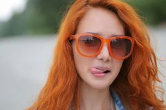Young red haired women posing in orange sunglasses with her tongue out Royalty Free Stock Photo