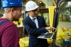Taking inventory at factory warehouse. Young red-haired worker and his mixed race superior with laptop in hands taking inventory at spacious warehouse of modern Stock Image