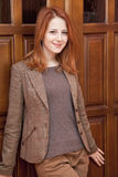 Young red-head girl near wooden doors. Royalty Free Stock Images