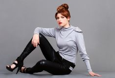 Young red head wearing leather pants Stock Photos