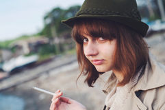 Young red head woman wearing fedora smoking Stock Photography