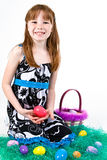 Young female sitting in fake grass with Easter eggs. A young red headed female child holding an Easter eggs in front of her. Sitting on fake grass with more Royalty Free Stock Images