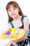 Young female child holding a plate of Easter eggs. A young red headed female child holding a plate of Easter eggs in front of her Royalty Free Stock Images