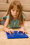 Young female child works on an over-sized calculator. A young red headed female child lays on the floor and works on an over-sized calculator Royalty Free Stock Photo