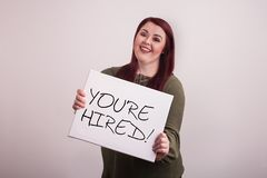 Young female woman holding a message board with You`re Hired written in black ink stock photos