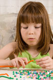 Young girl making bead bracelets. A young red headed girl making bead bracelets using pipe cleaners and numerous colorful plastic beads Royalty Free Stock Images