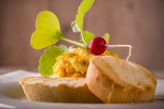 Young red radish on scrambled eggs with pastry Stock Photo
