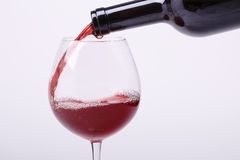Young red wine is poured into a glass Royalty Free Stock Photos