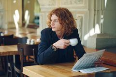 Young reddish man drinking coffee while looking to right Stock Images