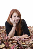 Young reddish woman lying in autumn leaves Royalty Free Stock Images