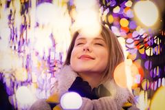 Woman in coat and scarf with Christmas time light royalty free stock image