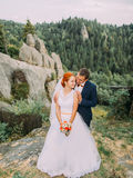 Young redhair bride and happy groom embracing on the background of rocky Carpathian mountains Royalty Free Stock Photo