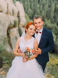 Young redhair bride and happy groom embracing on the background of rocky Carpathian mountains Royalty Free Stock Photography