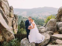 Young redhair bride and happy groom softly embracing on the background of rocky Carpathian mountains Royalty Free Stock Images