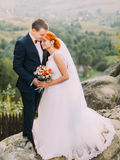 Young redhair bride and happy groom softly embracing on the background of rocky Carpathian mountains Stock Photography