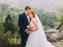 Young redhair bride and happy groom softly embracing on the background of rocky Carpathian mountains Royalty Free Stock Image