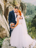 Young redhair bride and happy groom softly embracing on the background of rocky Carpathian mountains Royalty Free Stock Photos