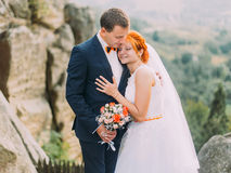 Young redhair bride and happy groom softly embracing on the background of rocky Carpathian mountains Stock Photos