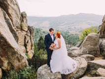 Young redhair bride and happy groom softly embracing on the background of rocky Carpathian mountains Royalty Free Stock Photography
