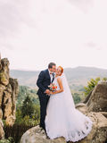 Young redhair bride and happy groom softly kissing on the background of rocky Carpathian mountains Royalty Free Stock Image