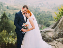 Young redhair bride and her loving groom softly embracing in rocky Carpathian mountains Royalty Free Stock Photos