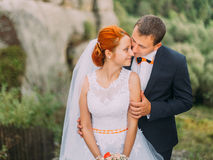 Young redhair bride turned to the groom on background of rocky Carpathian mountains Royalty Free Stock Photo