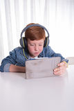 Young redhaired boy is looking a movie on a tablet Stock Images