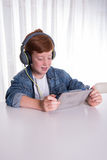 Young redhaired boy is looking a movie on a tablet Royalty Free Stock Photos