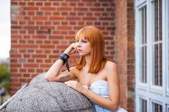 Young redhaired woman. Redhaired girl with a light-blue jeans dress Stock Image