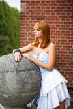 Young redhaired woman. Redhaired girl with a light-blue jeans dress Royalty Free Stock Images