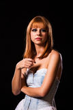 Young redhaired woman. Redhaired woman in a light-blue jeans dress in front of a black background Royalty Free Stock Photography