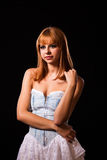 Young redhaired woman. Redhaired woman in a light-blue jeans dress in front of a black background Royalty Free Stock Images