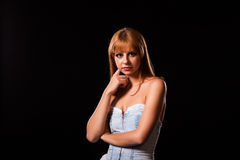 Young redhaired woman. Redhaired woman in a light-blue jeans dress in front of a black background Stock Photography