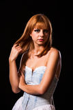 Young redhaired woman. Redhaired woman in a light-blue jeans dress in front of a black background Stock Images
