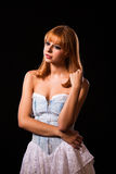 Young redhaired woman. Redhaired woman in a light-blue jeans dress in front of a black background Royalty Free Stock Photos