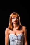 Young redhaired woman. Redhaired woman in a light-blue jeans dress in front of a black background Royalty Free Stock Photo
