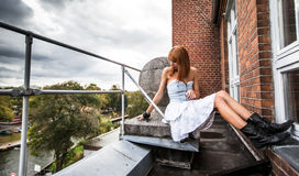 Young redhaired woman. In a light-blue jeans dress sitting on a balcony Royalty Free Stock Photography