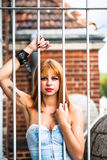 Young redhaired woman. Redhaired woman in a light-blue jeans dress standing behind white bars Stock Image