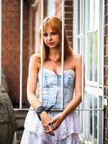 Young redhaired woman. Redhaired woman in a light-blue jeans dress standing behind white bars Royalty Free Stock Photo