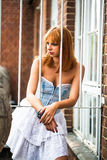 Young redhaired woman. Redhaired woman in a light-blue jeans dress standing behind white bars Royalty Free Stock Photography