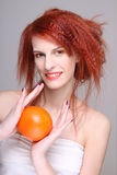 Young redhaired woman with orange in her hands. Over grey Royalty Free Stock Image