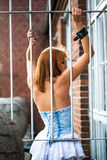 Young redhaired woman. Posterior view of a redhaired woman in a light-blue jeans dress standing behind white bars Royalty Free Stock Images
