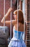 Young redhaired woman. Posterior view of a redhaired woman in a light-blue jeans dress standing behind white bars Stock Image