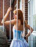 Young redhaired woman. Posterior view of a redhaired woman in a light-blue jeans dress standing behind white bars Stock Photography