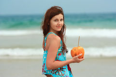 Young redhead on the beach with a coconut. Young white woman relaxing on the beach of a tropical destination drinking cocnut water from a whole nut Stock Image