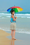 Young redhead on the beach with a rainbow umbrella Royalty Free Stock Images