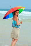 Young redhead on the beach with a rainbow umbrella Royalty Free Stock Photo