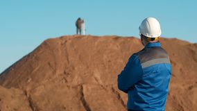 Young redhead bearded caucasian construction worker in blue uniform, protective glasses and hardhat helmet looks at stock video